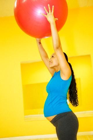 Mulher gestante fazendo Pilates
