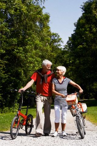 casal caminhando com bcicletas em parque - equilíbrio - dicas para prevenir quedas - blog do kaizen