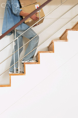 Pessoa carregando caixa subindo uma escada - equilíbrio - dicas para prevenir quedas - blog do kaizen