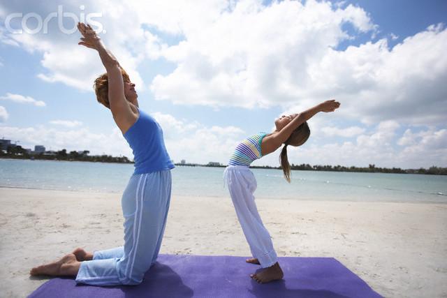 Mãe e filha praticando Yoga na praia - Yoga para crianças
