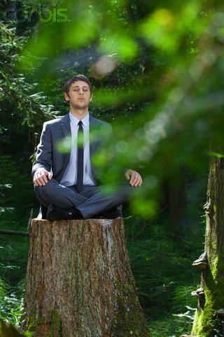 homem de terno meditando em parque
