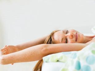 yoga em casa - mulher deitada na cama alongando