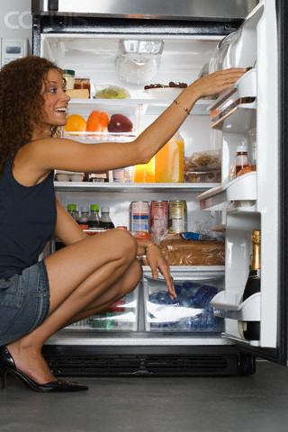 mulher olhando comida na geladeira -