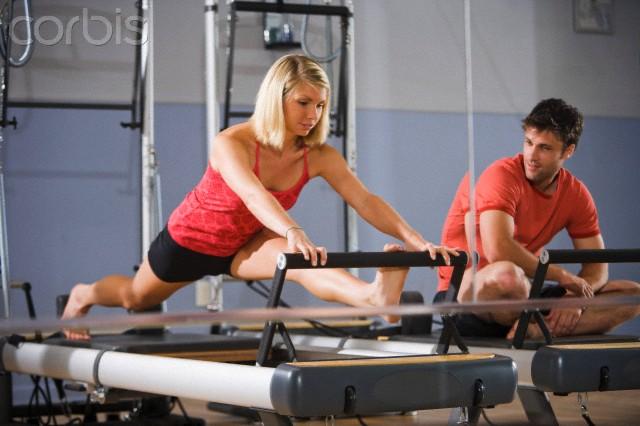 Casal praticando pilates no reformer