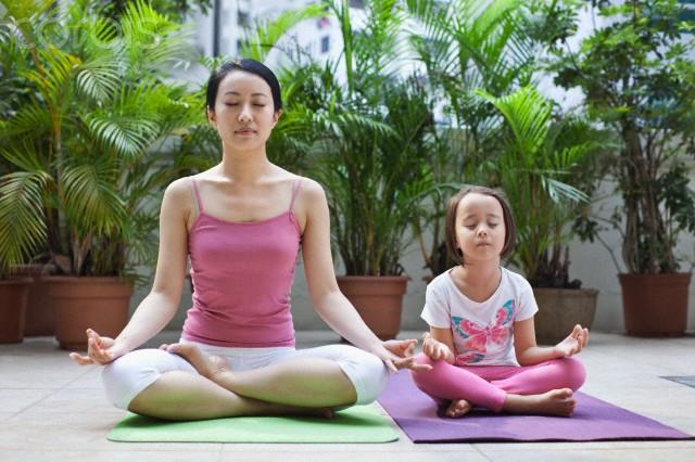 Mãe e filha na posição de lotus do Yoga