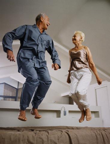 Casal de idosos pulando na cama - positividade