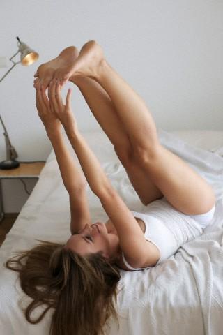 mulher alongando-se na cama-Pilates