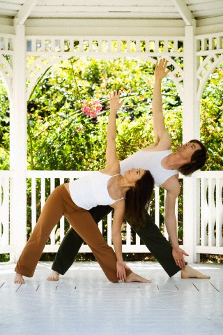 casal praticando yoga em gazebo