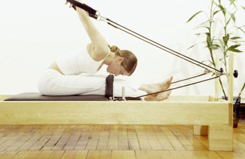 mulher praticando Pilates no reformer