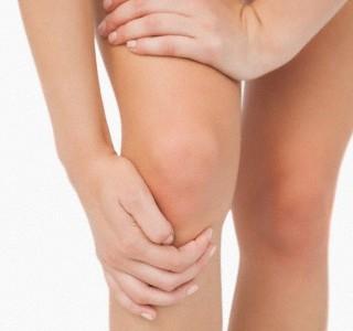 mulher segurando joelho com craibra