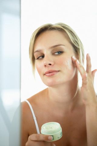 mulher aplicando creme na pele - limpeza de pele para acne