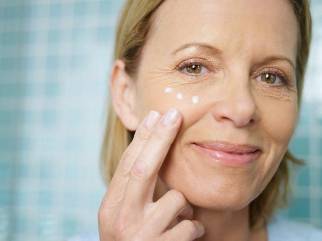 mulher aplicando creme no rosto - pele na menopausa