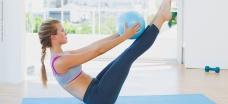 Moça praticando pilates no solo - QUAL O MELHOR HORÁRIO PARA PRATICAR PILATES