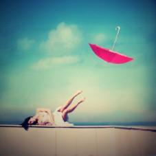 Moça deitada em praia e guarda-chuva voando - jornada para a sua verdade