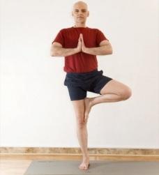 homem realizando a postura da árvore de Yoga