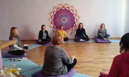 aula de yoga com alunos meditando sentados no chão