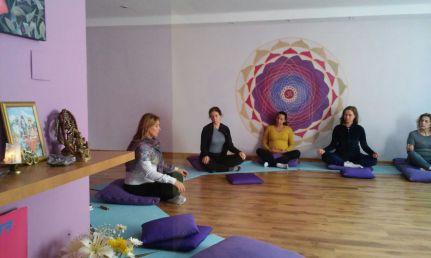 aula de yoga com professora e alunos meditando sentados no chão