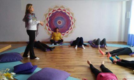 aula de yoga com pessoas deitadas em círculo no chão e professora caminhando