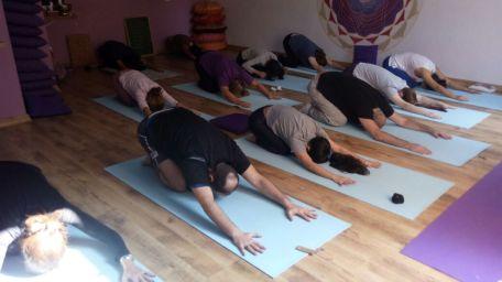 aula de yoga com pessoas em postura da criança vista de cima