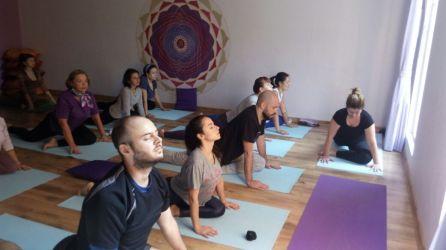 Aula de yoga com pessoas no chão realizando a postura de saudação ao sol