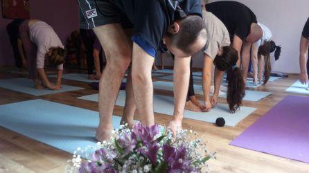 aula de yoga com destaque para aluno homem careca em pé se curvando para tocar os pés
