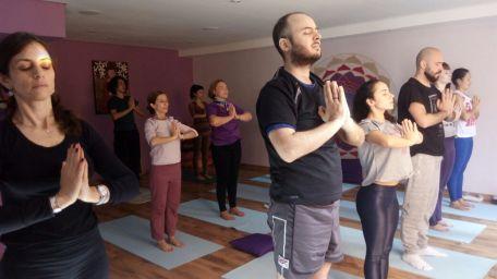 aula de yoga com pessoas em pé em posição de saudação
