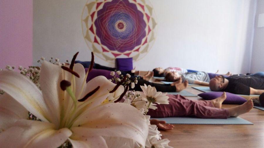 Aula de Yoga com pessoas deitadas meditando
