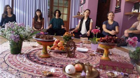 quatro moças sentadas no chão com objetos de yoga em primeiro plano