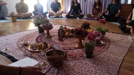 destaque para os objetos de yoga no centro do círculo formado por pessoas sentadas no chão