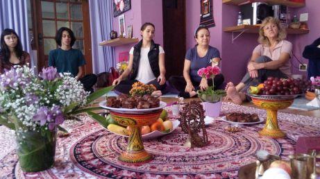 duas moças sentadas no chão com objetos de yoga em primeiro plano