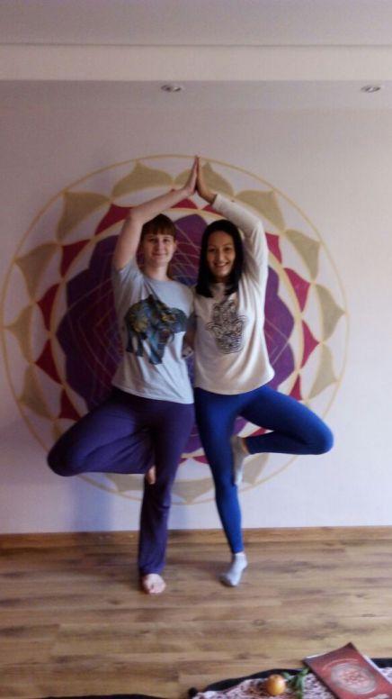 duas moças em posição de yoga unindo pés e mãos em pés e de frente com mandala lilás atrás