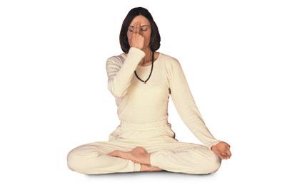 moça de branco e colar de contas pretas sentada de pernas cruzadas em posição de lótus com os dedos na mão direita repousados na testa