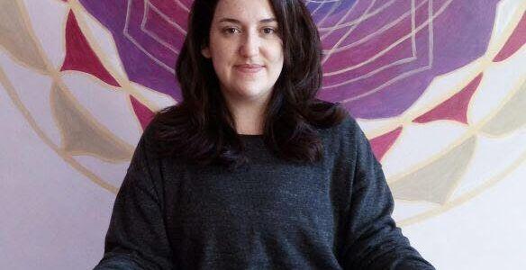 Mulher de cabelos castanhos sorrindo, roupa preta, sentada de pernas de índio e mãos repousadas nos joelhos de palmas para cima, com mandala roxa ao fundo