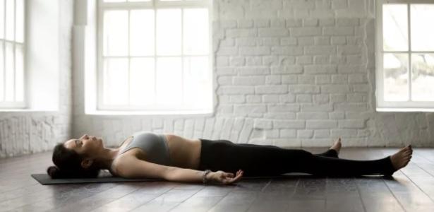 mulher deitada no chão de olhos fechadas com calça preta e top cinza realizando meditação