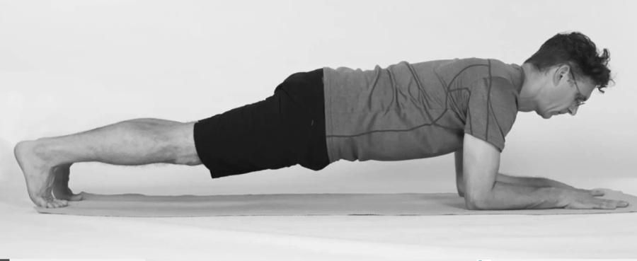 homem idoso fazendo a prancha baixa em tapete de Yoga, com óculos e foto preto e branco
