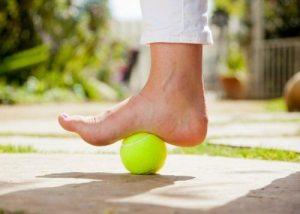 bola de tênis sendo pisada por pé com calça branca em ambiente externo