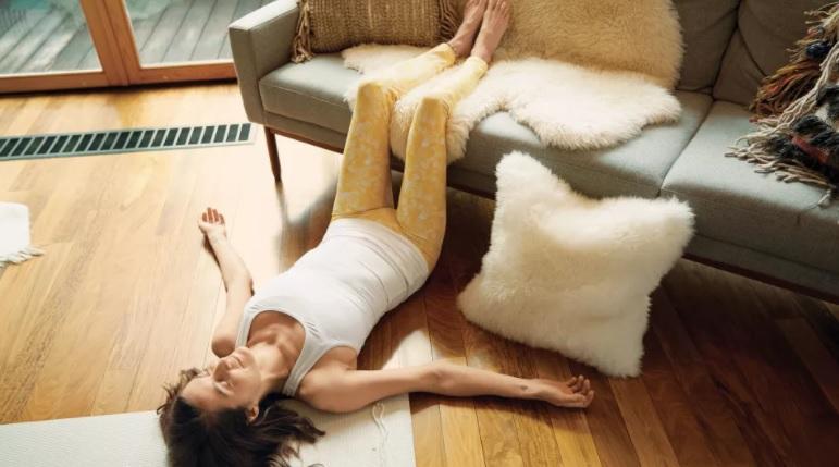 mulher com blusa branca e calça amarela deitada no chão com os braços abertos e as pernas apoiadas no sofá cinza com manta de pelúcia branca e almofada de pelúcia branca no chão apoiada em pé no sofá