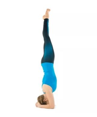 moça com blusa azul clara e calça azul escura realizando a posturs invertida com apoio de cabeça