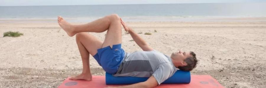 homem de meia idade com shorts azul claro e camiseta cinza deitado em rolinho na vertical em tapete rosa tocando a mão direita em perna esquerda com joelhos flexionados, ambiente de praia