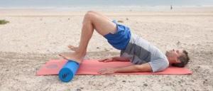 homem de meia idade com shorts azul claro e camiseta cinza deitado em rolinho na vertical em tapete rosa, pés apoiados no rolinho na horizontal, joelhos flexionados, quadril elevado, ambiente de praia
