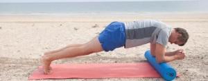 homem de meia idade com shorts azul claro e camiseta cinza deitado em rolinho na vertical em tapete rosa, com antebraços apoiados no rolinho na horizontal, pernas estendidas com pés em meia ponta apoiados no solo, em prancha baixa, ambiente de praia