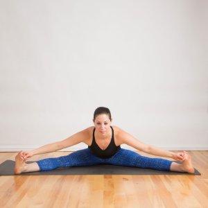 moça de calça azul e blusa preta sentada com perna abertas tocando os pés com as mãos