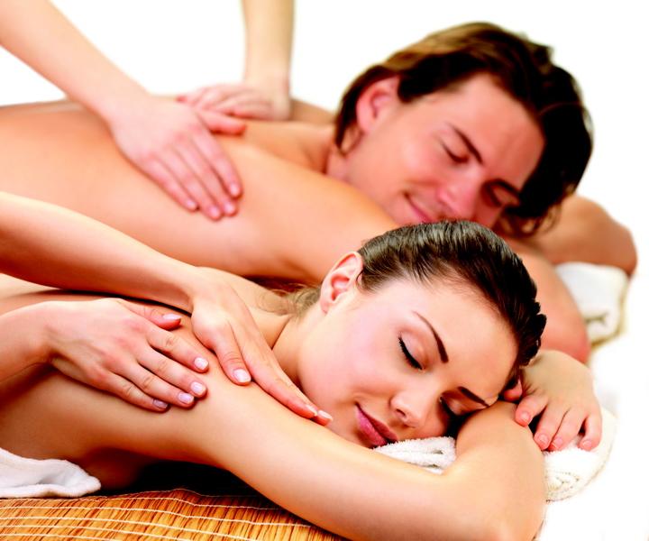 casal deitado lado a lado realizando massagem relaxante