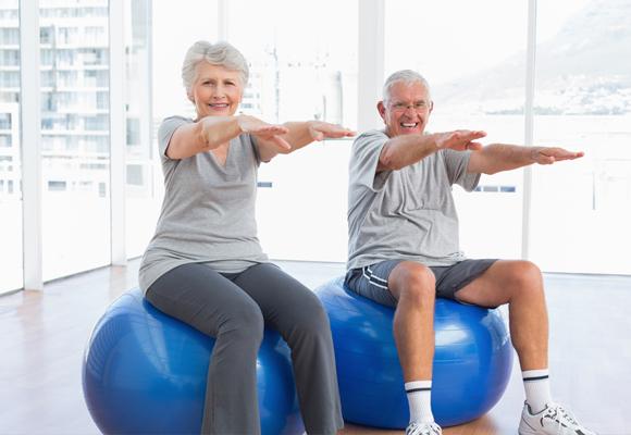casal de idosos sorrindo sentados em bolas de Pilates azuis cim braços alongados à frente. Vestem roupa cinza