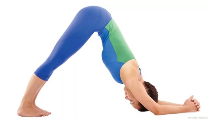 mulher com calça azul claro e blusa verde com azul realizando a postura