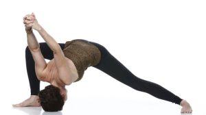 mulher de calça preta e blusa marrom realizando a postura