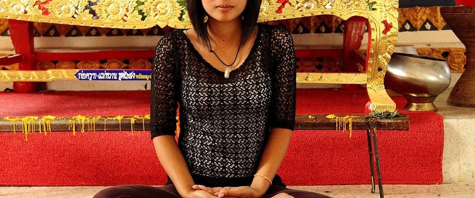 moça asiática de cabelos pretos, lisos e curtos, meio presos na franja, deroupa preta, sentada no chão, fundo e tapetes vermelhos com móvel dourado atrás, pernas cruzadas e mãos unidas repousadas nos pés