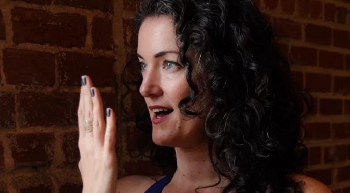 moça de cabelo enrolados com boca aberta e palma da mão virada para a boca