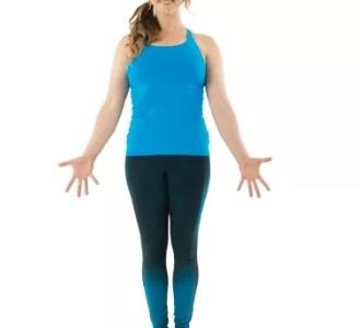 moça de cabelos enrolados e presos, blusa azul e calça azul escura que vai ficando clara dos joelhos para baixo, realizando a postura
