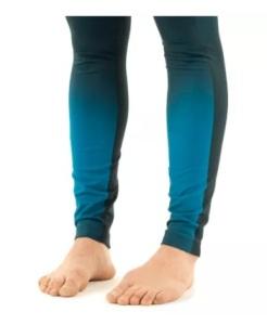 moça de cabelos enrolados e presos, blusa azul e calça azul escura que vai ficando clara dos joelhos para baixo, em close nos pés que estão desalinhados pois o peso do corpo está nas laterais